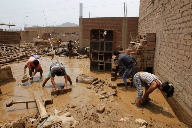 People remove mud from a house after a landslide and flood in Lurigancho distric