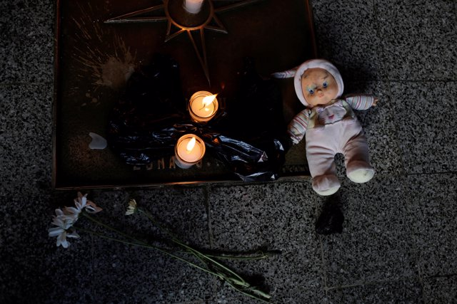 A doll and candles are placed during a protest to demand justice for the victims