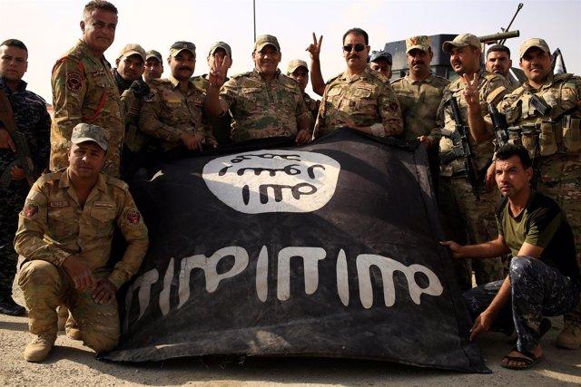 Soldados iraquíes posan con la bandera de Estado Islámico