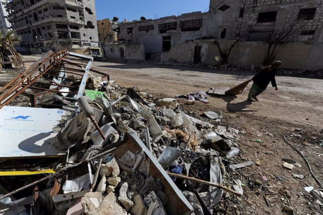 A woman walks past debris along a street in Aleppo's Belleramoun Industrial Zone