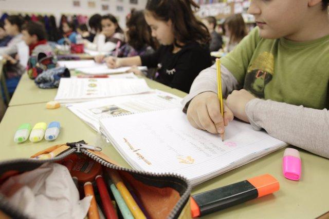Escolares hacen deberes provistos de rotuladores, cuadernos y material escoalr