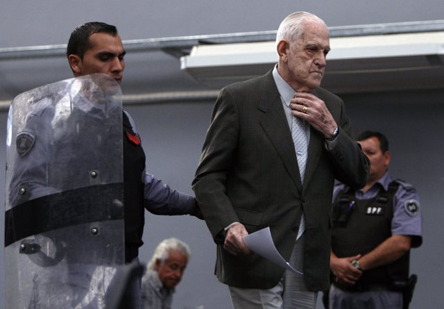 Reynaldo Bignone, a former general who ruled Argentina in 1982-1983, is escorted