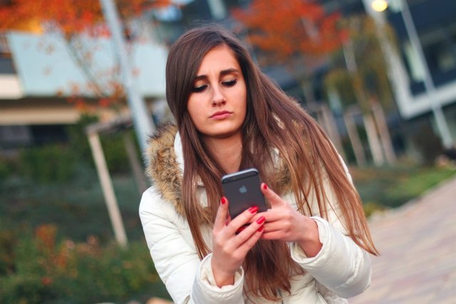 Adolescente, mujer usando su teléfono móvil, smartphone