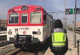 Una agente ante un tren de cercanías en la estación de Alacant Terminal