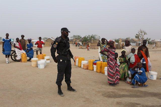 Un policía camerunés junto a refugiados nigerianos en Minawao