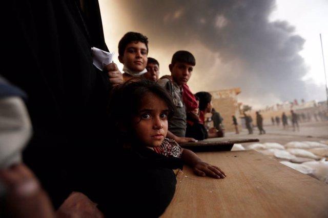 Niños esperando para recibir comida a las afueras de Mosul