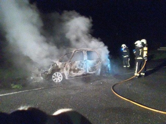 Bomberos sofocando el fuego en el vehículo