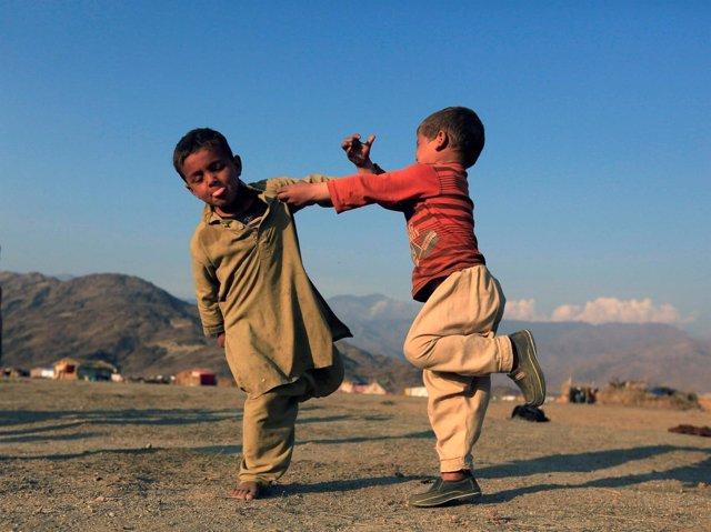 VArios niños afganos juegan en un campo de desplazados en Afganistán.
