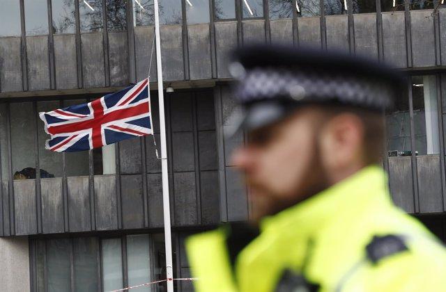 Policía con la bandera británica al fondo
