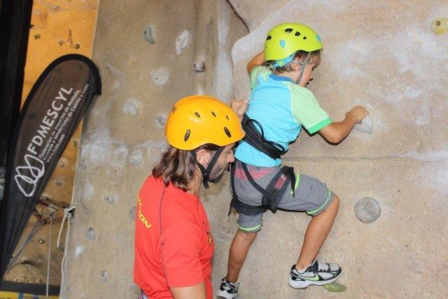 Jóvenes practicando la escalada en el rocódromo.