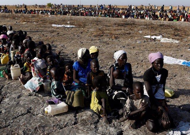 Mujeres y niños esperan una distribución de alimentos en Sudán del Sur