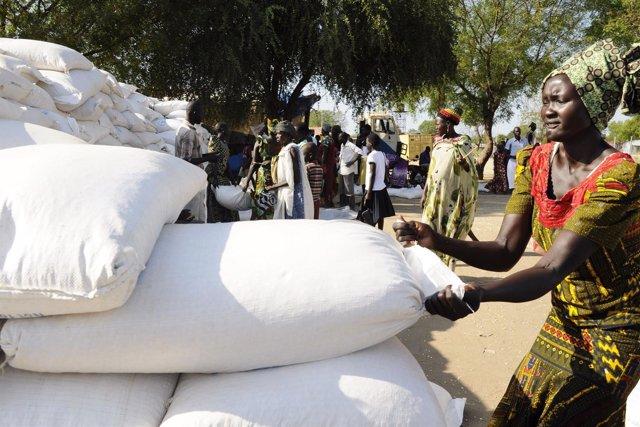 Una mujer sursudanesa coge un saco de cereales en la localidad de Bor.