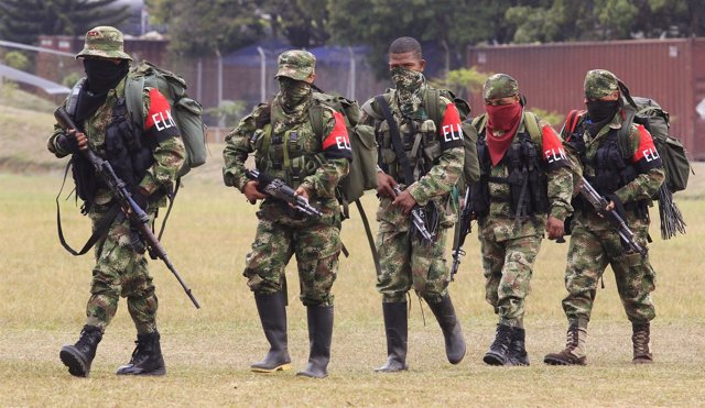 Defected members of Colombian guerrilla group ELN walk to a military base to sur