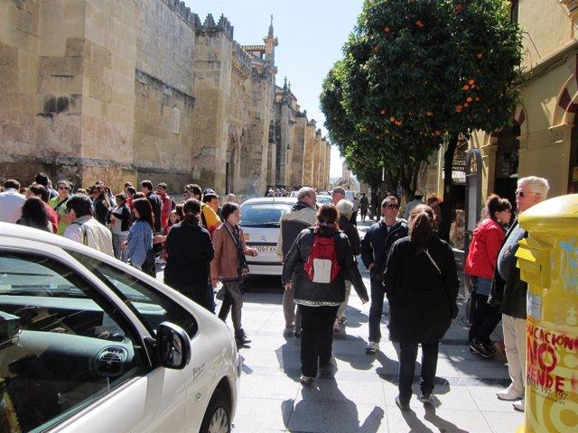 Los turistas andan entre los taxis ubicados en la acera de la calle Torrijos