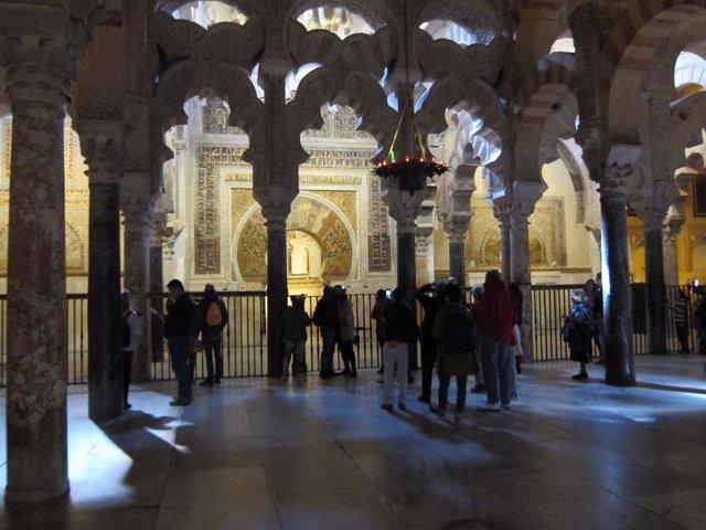 Turistas ante el Mihrab de la Mezquita, del que les separa una valla
