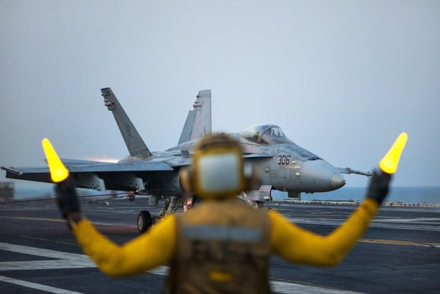 Aviation Boatswain's Mate (Handling) 2nd Class Ted Casal directs an F/A-18C Horn