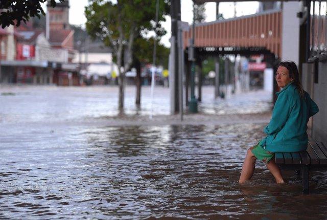 Mujer en una calle inundada en Australia por el ciclón Debbie