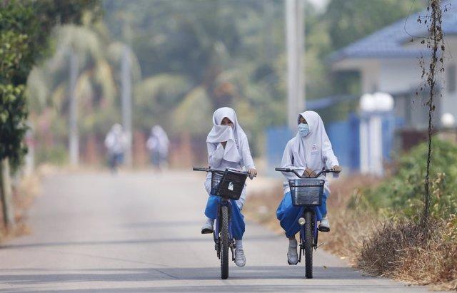 Niñas volviendo de la escuela en bicicleta