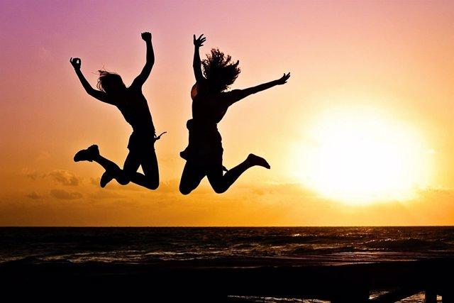 Gente saltando de felicidad al atardecer.