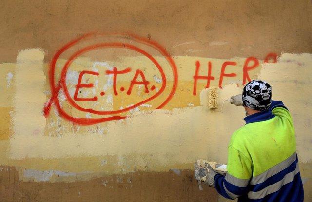 Un hombre borra una pintada de ETA en Guernica, Euskadi