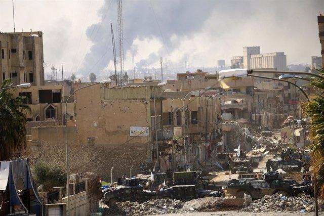 Una calle de Mosul y columnas de humo al fondo