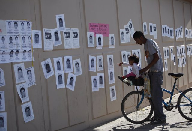 Niña señala fotos de los desaparecidos en Ayotzinapa