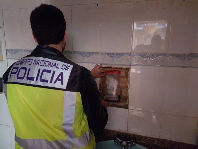 Un agente ante el hueco donde  escondían 4 kilos de cocaína