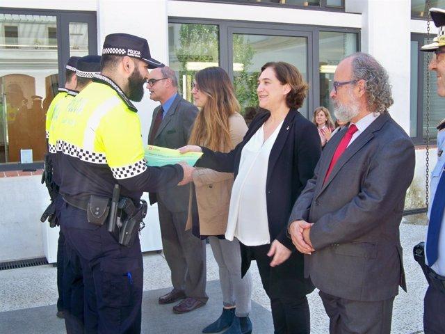 La alcaldesa de Barcelona Ada Colau entrega un diploma a un policía de barrio