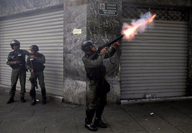 Un policía venezolano dispara gas lacrimógeno durante la marcha de la oposición.