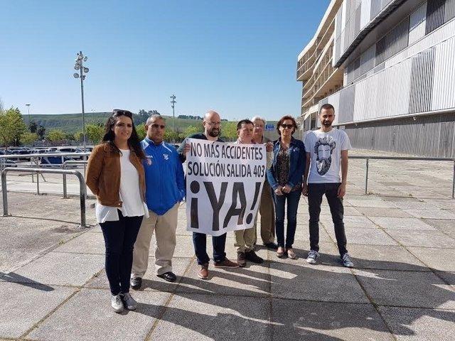 González (izda.) junto a la pancarta por una solución para la salida 403