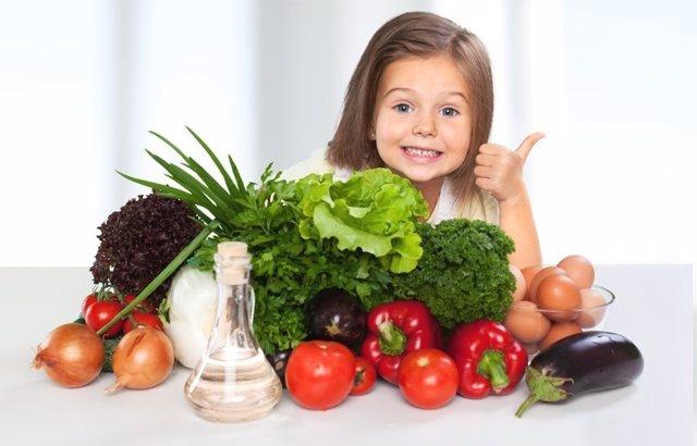 Dieta sana en niños. Niña comiendo verduras y hortalizas