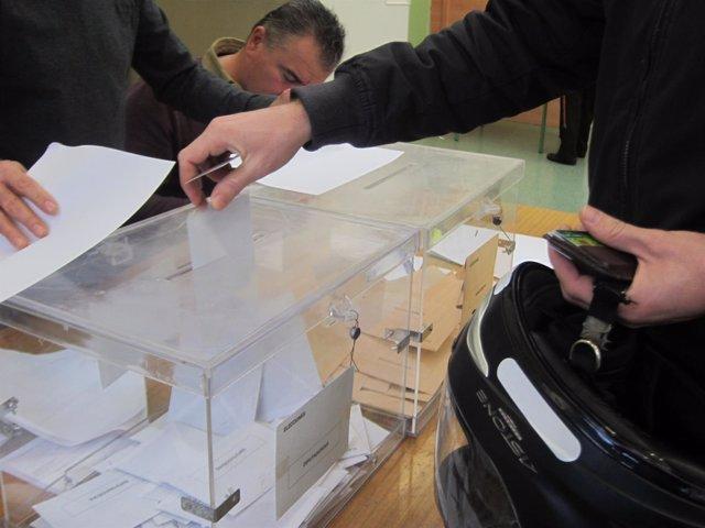 Un joven con casco deposita el voto al Congreso en la urna