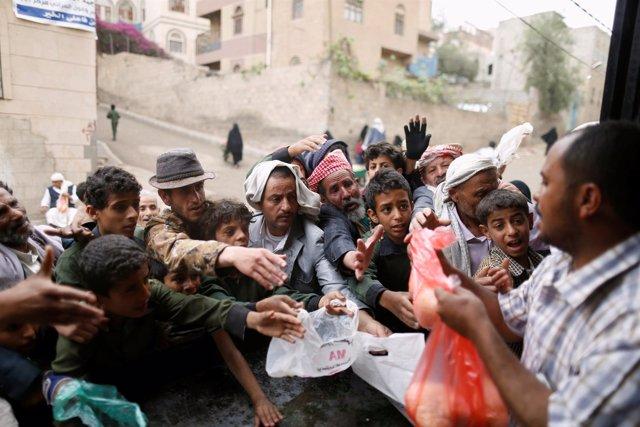 Civiles yemeníes se reúnen para recoger alimentos en Saná, Yemen.
