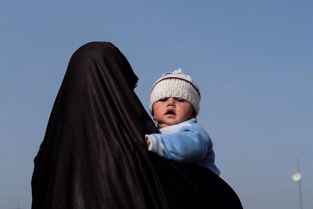 Una mujer iraquí desplazada de Mosul con su bebé