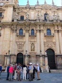 Un Grupo De Turistas Atiende Las Indicaciones Del Guía Ante La Catedral De Jaén.