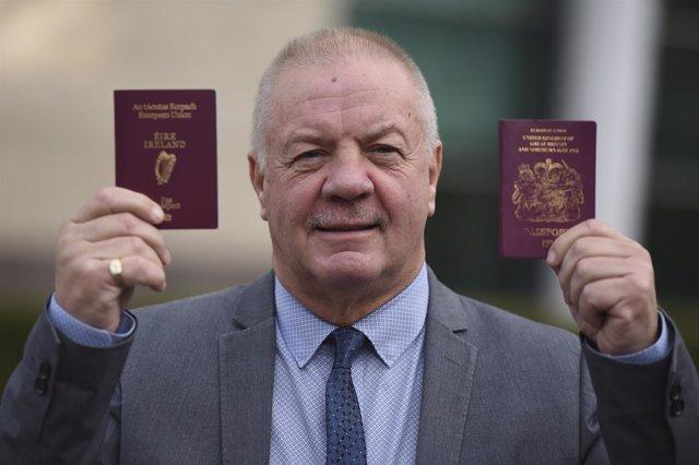 Raymond McCord mostrando un pasaporte irlandés y un de Reino Unido