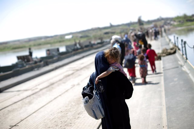 Mujer iraquí huyendo de Mosul en un puente