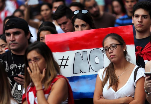 A protester holds a sign in the colours of Paraguay's national flag that reads N