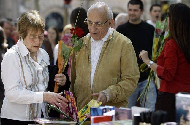 Una pareja mira un libro con un rosa en la mano en Sant Jordi