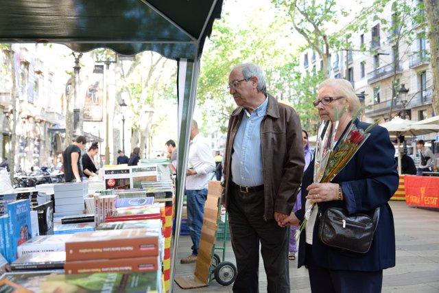 Parella amb una rosa a un stand de llibres per Sant Jordi