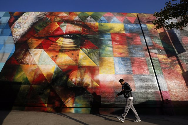 A man walks past a mural of Nelson Mandela painted by Brazilian artist Eduardo K