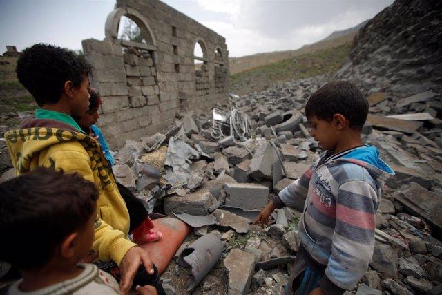 Niños junto a una casa destruida en un bombardeo en Saná