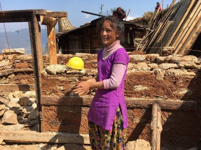 Mujer ayuda en la reconstrucción de su casa en Nepal