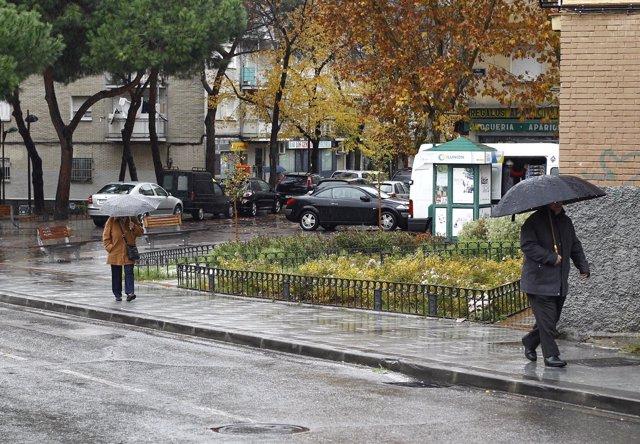 personas bajo sus paraguas.