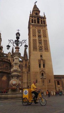 Triciclo de Correos ante la Giralda de Sevilla