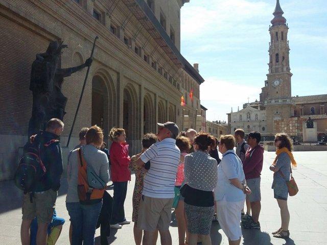 Un grupo de turistas visitan la plaza del Pilar.