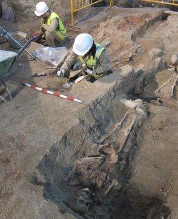 Dos arqueólogos trabajan con restos óseos aparecidos en Iglesia de la Magdalena