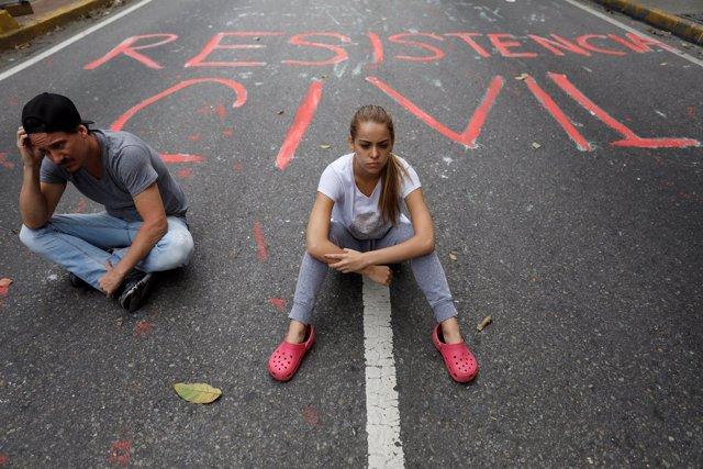 Manifestantes opositores en Caracas con graffiti 'Resistencia Civil'