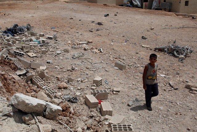 Un niño camina por una calle en Deraa