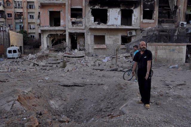 Un hombre señala un crater producido por una bomba barril en Yarmuk (Siria)